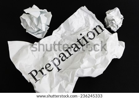 Crumpled paper sheet with word Preparation isolated on black - stock photo