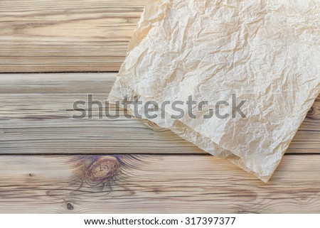 Crumpled piece of parchment on wooden boards - stock photo
