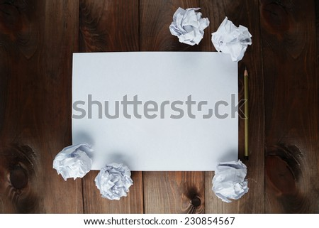 Crumpled up papers with a sheet of blank paper and a pencil on brown wooden background - stock photo