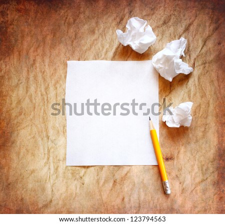 crumpled up papers with a sheet of blank paper and pencil - stock photo