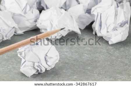 crumpled waste paper and pencil on gray background (select focus at front subject) - stock photo