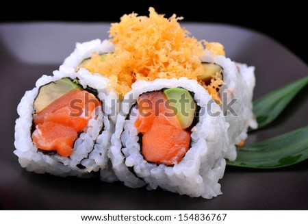 Crunch salmon roll maki sushi in black background decorate with leaf - stock photo
