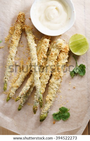 Crunchy baked asparagus fries with mayonnaise dip, healthy vegetable snack - stock photo