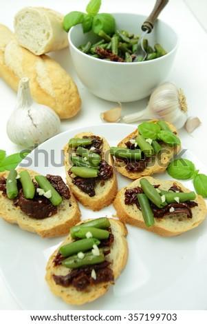 Crunchy bruschettas with dry tomatos, green bean, garlic and fresh basil leaves - stock photo