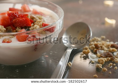 Crunchy fruit muesli (whole grain oats) served with fresh strawberries, raisins and low fat yogurt mixed with strawberry smoothie in a glass bowl - healthy breakfast - stock photo