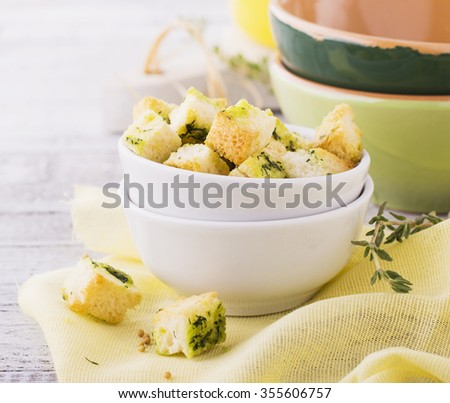 Crunchy homemade croutons with herbs and butter to the soup in a simple light wooden background. selective Focus - stock photo