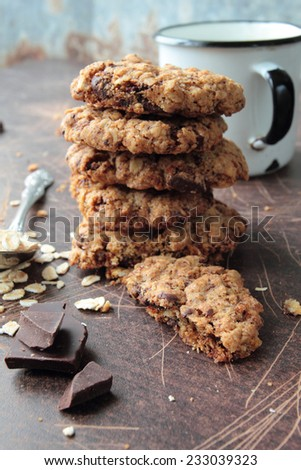 Crunchy oat cookies with dark chocolate and mug of milk - stock photo