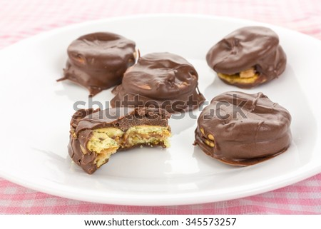 Crunchy peanut butter on salty crackers coated with creamy chocolate.  Selective focus and shallow dof with one partially eaten. - stock photo