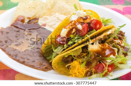 Crunchy Taco Mexican Plate with refried beans and spicy cheese dip on brightly colored Hispanic Place Mat.  Closeup with selective focus. - stock photo