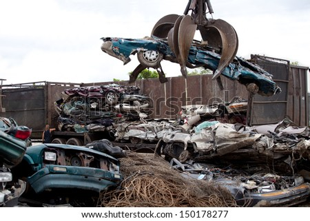 Crushed cars being picked up by a grabber - stock photo