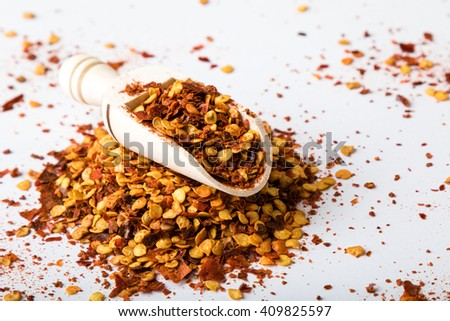 crushed dried chili flakes on white table with scoop - stock photo