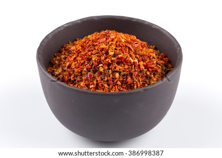 Crushed red chili pepper in stone bowl on white background - stock photo