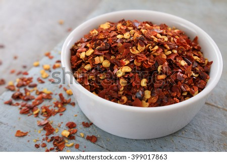 crushed red chillies in white dish - stock photo