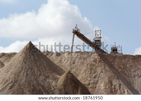 Crushed stone pouring off an elevated conveyor onto a large pile - stock photo
