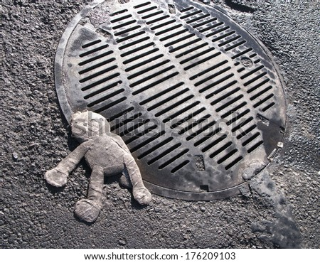 crushed toy doll on manhole cover - stock photo