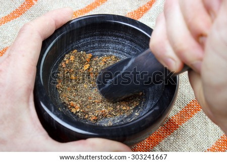 Crushing and grinding dried black peppers and chili to powder on mortar for seasoning food - stock photo
