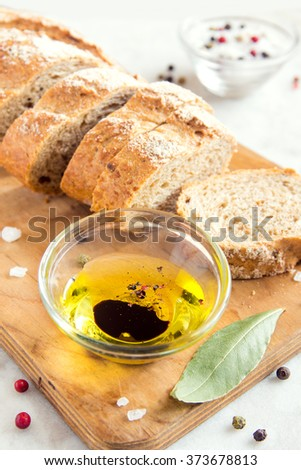 Crusty bread ciabatta and bowl of olive oil with balsamic vinegar, sea salt and spices close up - stock photo