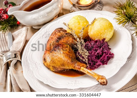Crusty Christmas goose leg with braised red cabbage and dumplings - stock photo