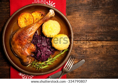 Crusty goose leg with braised red cabbage and dumplings. Cooking at Christmas time - stock photo