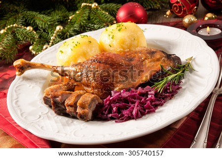 Crusty goose leg with braised red cabbage and dumplings on Christmas decorated table - stock photo