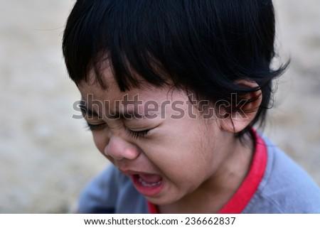 cry little boy on the beach closeup - stock photo