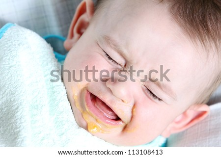 Crying baby boy eating vegetable mash - stock photo