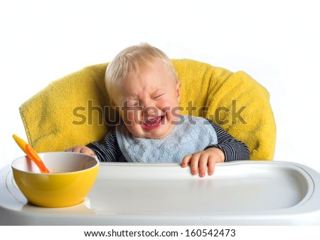 Crying baby boy, not wanting to eat - stock photo