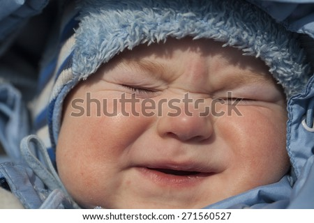 crying baby boy.warmly dressed overalls and cap crying - stock photo