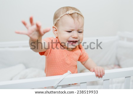 crying baby girl standing in the infant bed. She is having teeth pain - stock photo