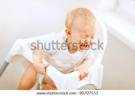 Crying baby in baby chair - stock photo