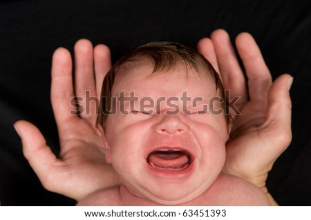 crying baby in protective hands - stock photo