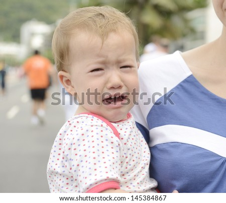 Crying baby on mother�´s arm - stock photo