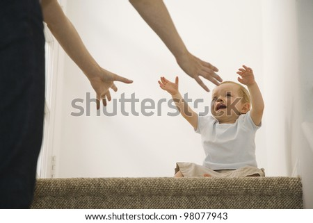 Crying baby reaching for mother - stock photo