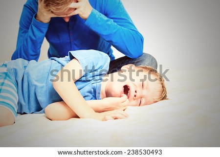 crying child, tired father- difficult parenting - stock photo