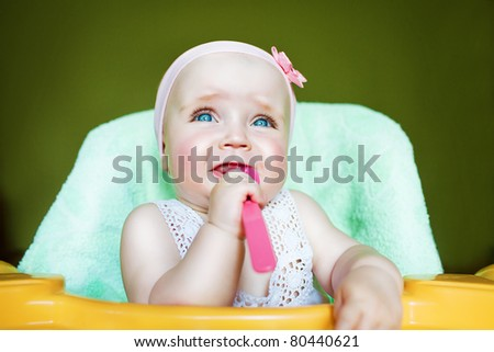 crying child with spoon in mouth - stock photo