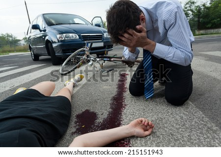 Crying driver and injured woman at road accident scene, horizontal - stock photo