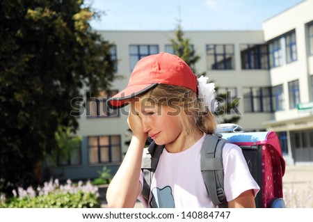 crying girl in front of the school - stock photo