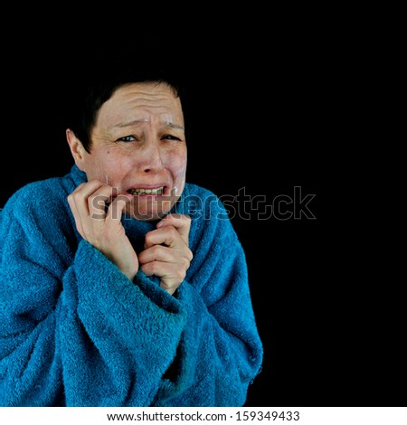Crying, hysterical, depressed woman in bath robe, applying face cream. Isolated against black background. - stock photo