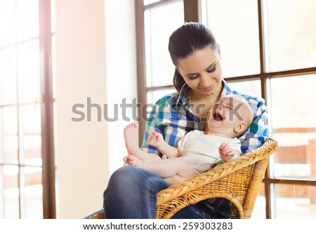 Crying little baby in the arms of her mother in a living room. - stock photo