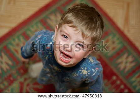 Crying little boy asks his mother's candy. - stock photo