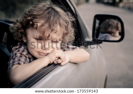 crying little boy sitting in the car - stock photo