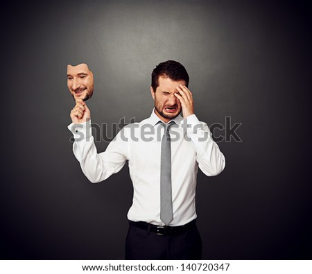crying man holding mask with smiley face - stock photo