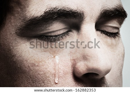 Crying man with tears on face closeup - stock photo