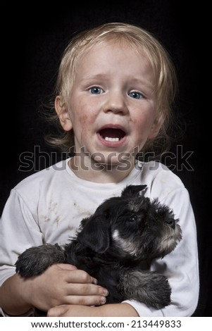 crying poor child embracing a puppy - stock photo