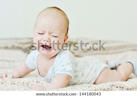 crying sweet   baby laying on the sofa - stock photo
