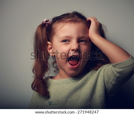 Crying unhappy girl with open mouth holding hand the head on dark background. Closeup portrait - stock photo
