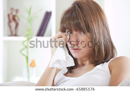 crying young woman with handkerchief in bed - stock photo