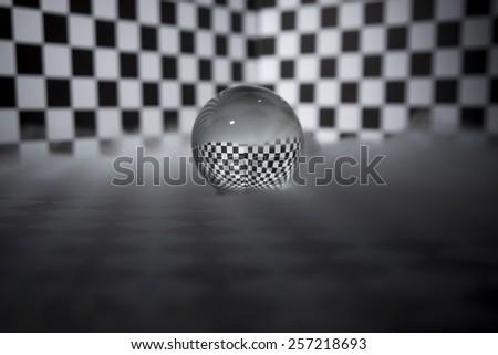 Crystal ball on a checkered background and in a fog. - stock photo