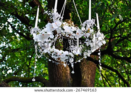Crystal Chandelier with candles and flowers against the background of green trees. - stock photo