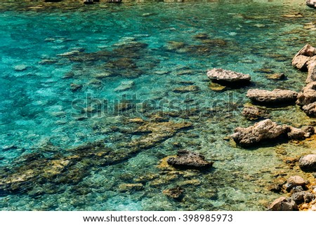 Crystal clear emerald water and sandstone rocks on the shore of the Mediterranean Sea, Cyprus - stock photo